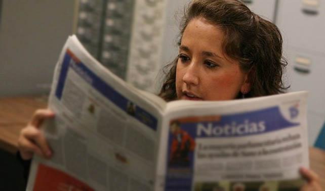 Joven sorprendida ante extraño tablet de papel con noticias viejas