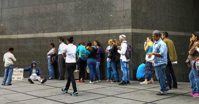 Venezolanos hacen cola para sacar efectivo de vaso de indigente