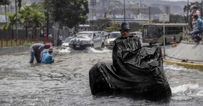 Lluvias hacen que motorizado se meta en bolsa negra para llegar a su casa