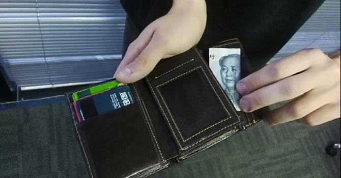 Joven mete yuan de la suerte en la cartera luego de tener que usar su dólar para comprar cigarro detallado