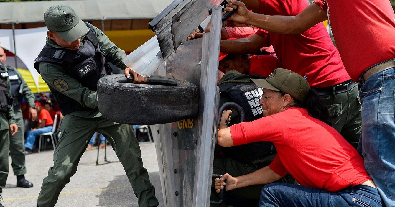 Milicianos entrenan en caso de que fuerza militar extranjera ataque con cauchos viejos