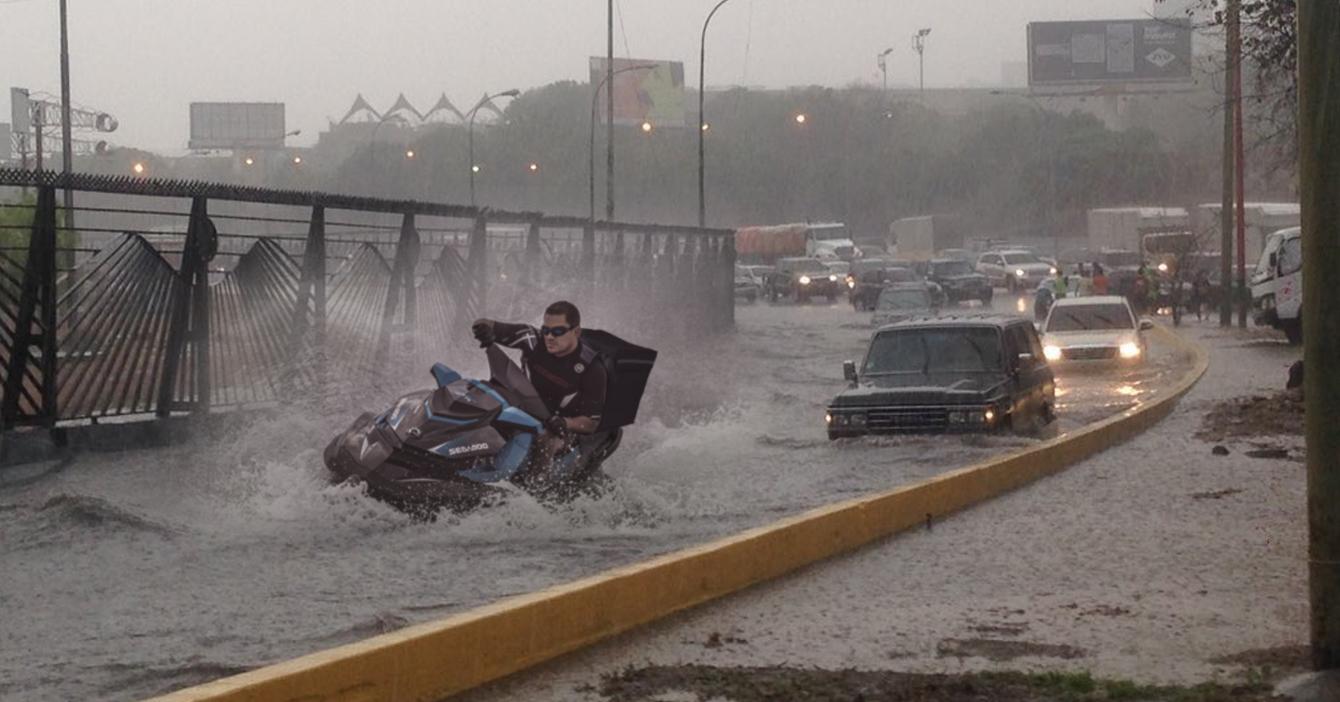 Lluvias hacen que delivery salga en moto de agua